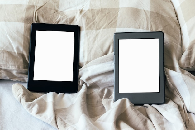 Dois livros eletrônicos modernos com telas vazias em branco em uma cama branca e bege. comprimidos na cama