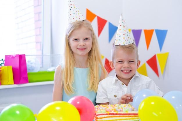 Dois loiros caucasianos crianças menino e menina em chapéus de aniversário, olhando para a câmera e sorrindo na festa de aniversário. fundo colorido com balões e bolo arco-íris de aniversário.