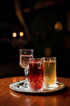 Dois long drink coquetéis com gelo em taças vintage e uma taça de vinho ou vermute em uma bandeja de prata
