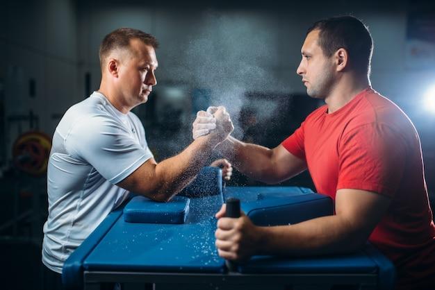 Dois lutadores de braço lutando com as mãos na mesa com alfinetes