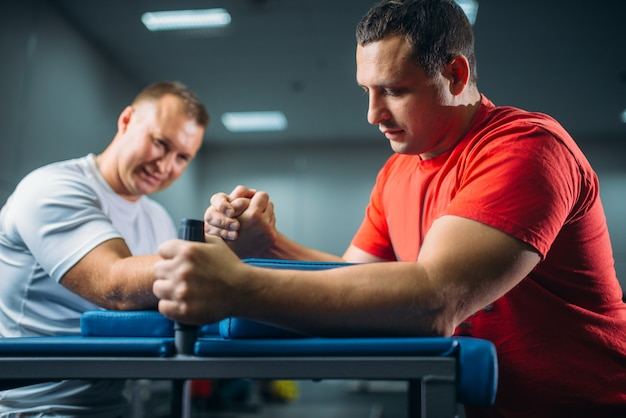 Dois lutadores de braço lutando em suas mãos na mesa com pinos, batalha em ação, competição de luta livre.