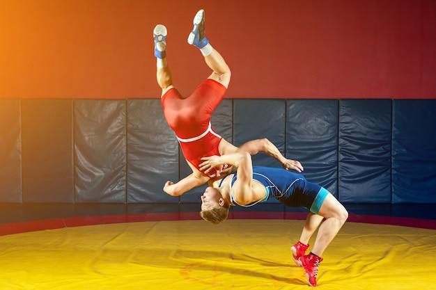 Dois lutadores fortes, de meia-calça azul e vermelha, estão fazendo um quadril em um tapete de luta amarelo no ginásio.
