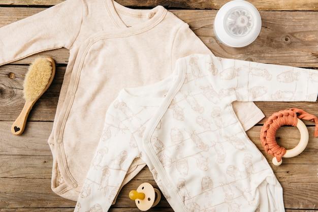 Dois macacão de bebê; escova; garrafa de leite; brinquedo e chupeta na mesa de madeira