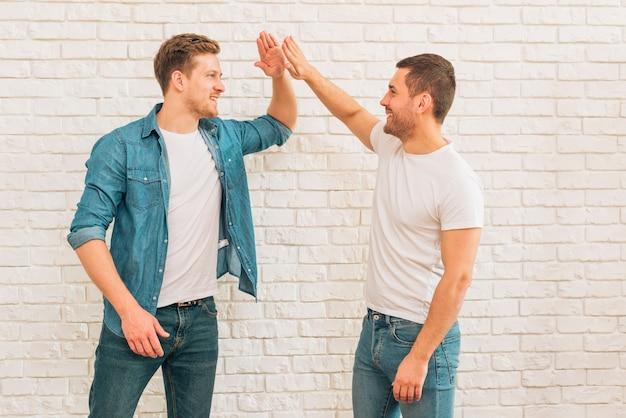 Dois, macho, amigos, dar, alto, cinco, para, um ao outro, contra, parede branca tijolo