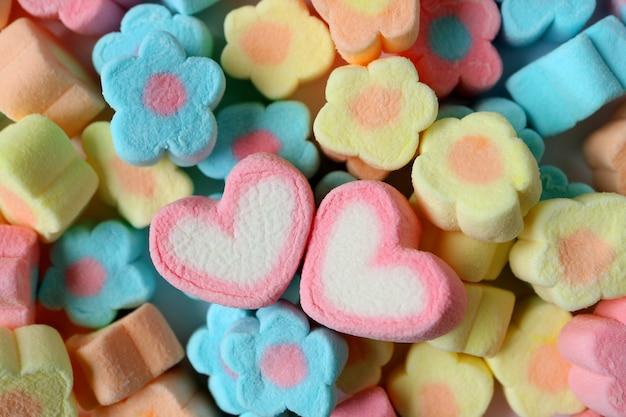 Dois marshmallows em forma de coração rosa e branco na pilha de marshmallows de flores pastel