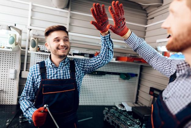 Dois mecânicos dão cinco uns aos outros para um bom trabalho.
