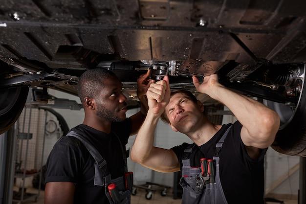 Dois mecânicos de automóveis inter-raciais uniformizados, verificando o carro no serviço automotivo