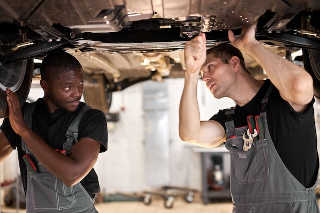 Dois mecânicos diversos inter-raciais verificando o fundo do carro no serviço automotivo