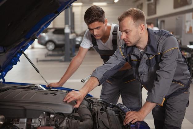 Dois mecânicos masculinos trabalhando na garagem