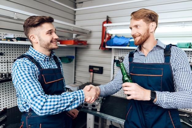 Dois mecânicos na estação de serviço. beber cerveja.