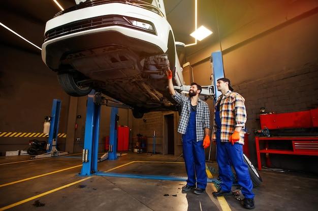 Dois mecânicos verificando a suspensão do carro na oficina de reparos