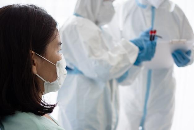 Dois médicos asiáticos usam terno de epi com máscara n95 e protetor facial, tratam e usam máscara de oxigênio com paciente infectado por coronavírus na sala de pressão negativa.