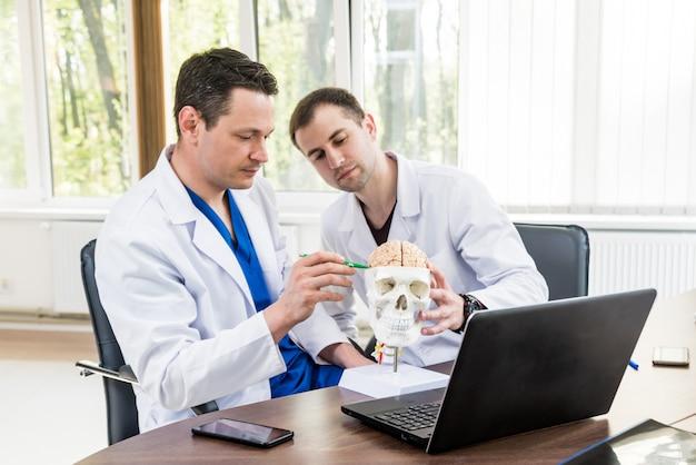 Dois médicos com conselho médico no hospital. discutir questões médicas antes da cirurgia no cérebro