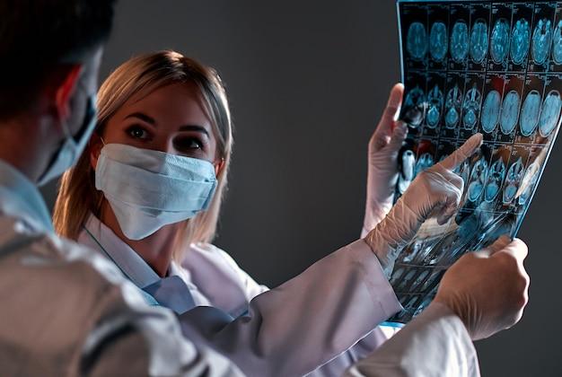 Dois médicos com máscaras protetoras olham e discutem um raio-x ou ressonância magnética do cérebro do paciente isolado no preto.