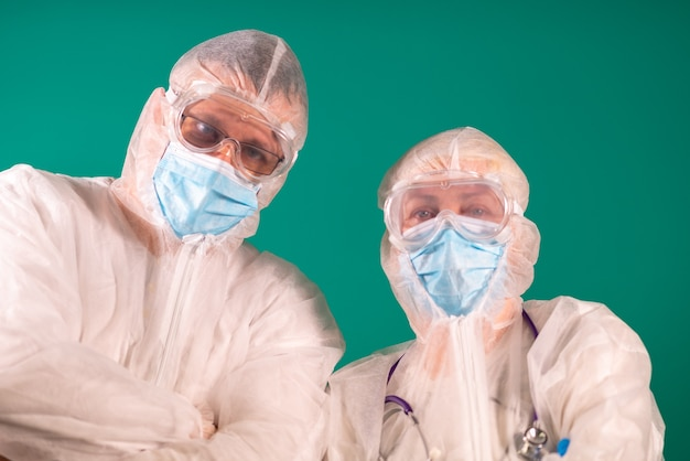 Dois médicos com protetores faciais em uniformes de traje de proteção individual e usando máscaras de proteção médica