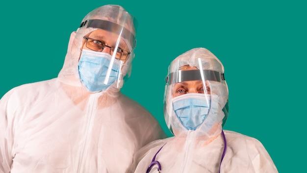 Dois médicos com protetores faciais em uniformes de traje de proteção individual, usando máscaras de proteção médica
