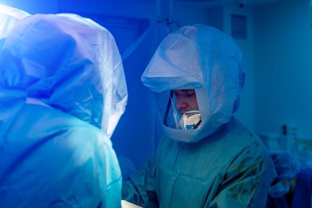 Dois médicos em equipamentos de proteção individual, incluindo terno branco para proteger a infecção covid 19. operação cirúrgica.