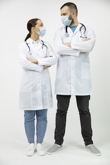 Dois médicos em máscaras médicas se olham em pé com os braços cruzados