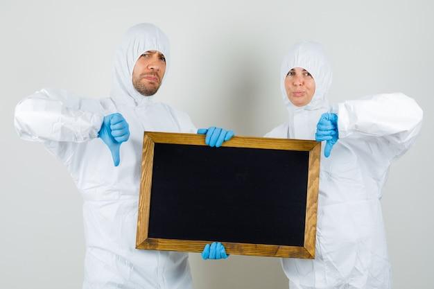 Dois médicos em trajes de proteção, luvas segurando uma lousa