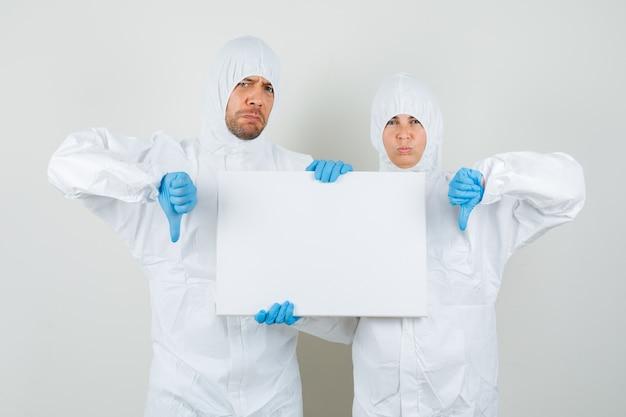 Dois médicos em trajes de proteção, luvas segurando uma tela em branco