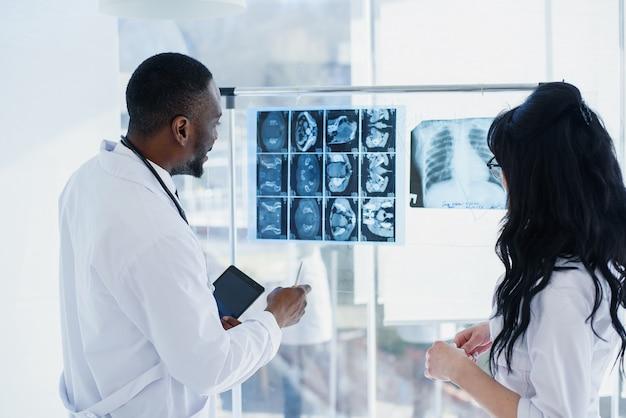 Dois médicos estão olhando para raios-x. médico. vista traseira do médico chefe afro-americano homem e mulher caucasiana, olhando para um raio-x mri na luz clara