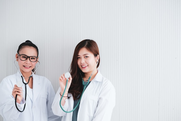 Dois médicos femininos com fones de ouvido em pé no hospital.