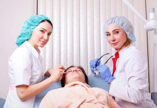 Dois médicos femininos examinando paciente após cirurgia plástica