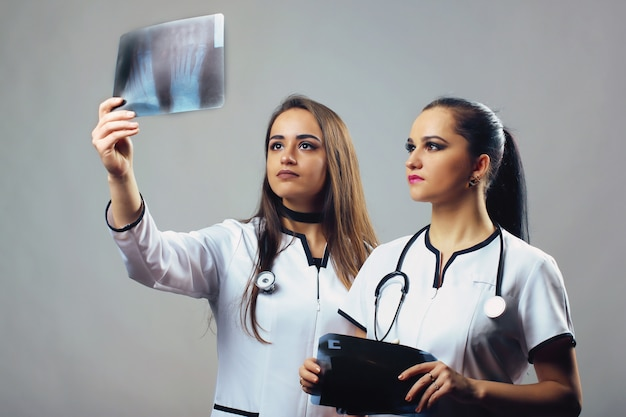 Dois médicos femininos olhando o raio x o conceito de saúde, medicina e radiologia