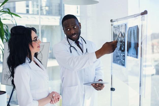 Dois médicos olham para um raio-x e discutem o problema. técnicos de medicina apontando para ressonância magnética do paciente. radiologista, verificação de raio-x. conceito de medicina e radiologia.