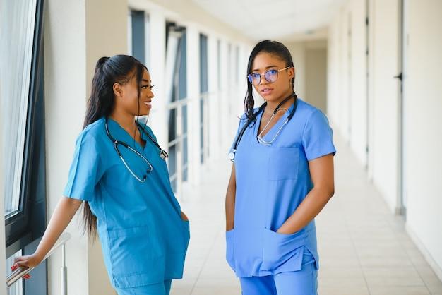 Dois médicos ou enfermeiras alegres amigáveis femininos no escritório.