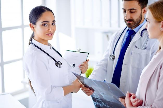 Dois médicos se comunicam com um paciente e mostram um raio-x para um paciente em um hospital