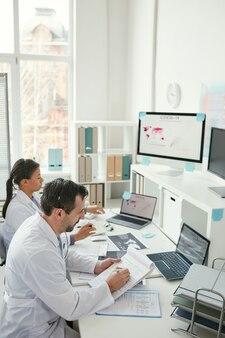 Dois médicos sentados à mesa e fazendo anotações em documentos juntos durante seu trabalho no escritório