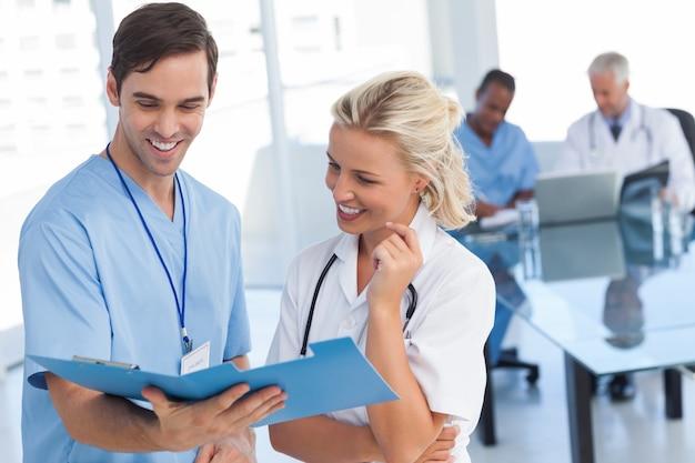 Dois médicos sorridentes falando sobre um arquivo azul