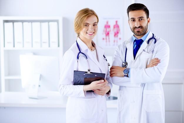 Dois médicos, todos juntos em uma sala de consultoria e segurando anotações do paciente