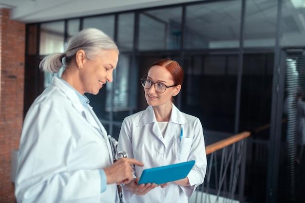 Dois médicos. vista lateral de uma médica sênior sorridente com um tablet em pé no corredor ao lado de seu colega