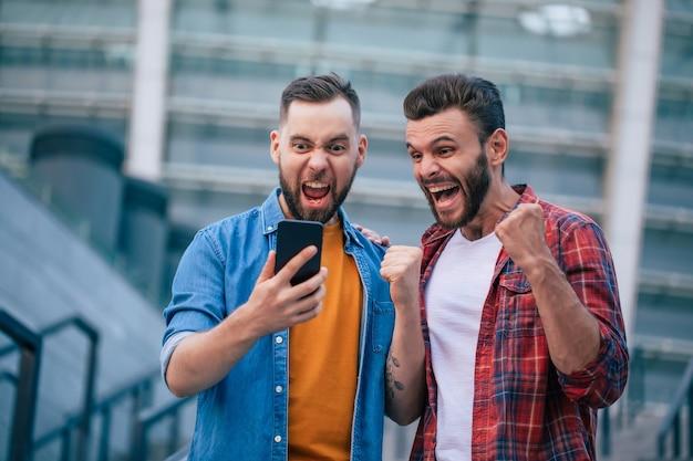 Dois melhores amigos ao ar livre. caras animados e felizes por ganharem aposta com smartphone