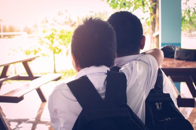 Dois melhores amigos de menino pensando e abraçando com amor