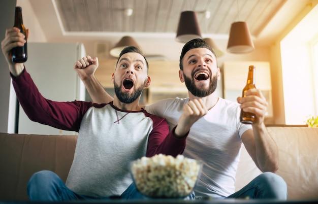 Dois melhores amigos e fãs de futebol assistindo a algum jogo esportivo na tv e bebendo cerveja e comendo lanches enquanto torcem pelo time no sofá