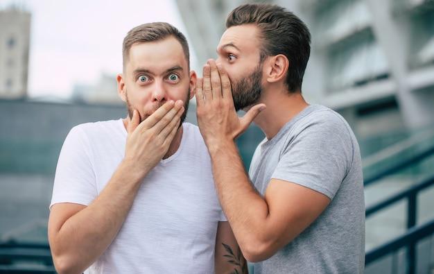 Dois melhores amigos engraçados e animados em roupas casuais estão fofocando e conversando ao ar livre.