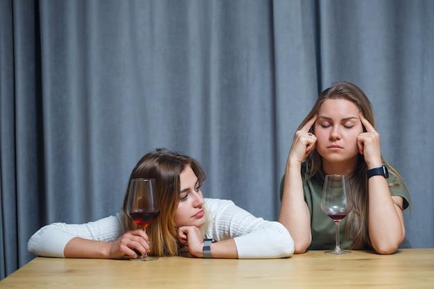 Dois melhores amigos. jovens mulheres de aparência europeia conversando, sentado em uma mesa segurando uma taça de vinho. lindas meninas, as irmãs adoram beber álcool, rindo, alegres, relaxando na sala de estar