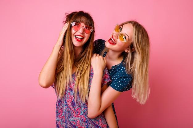 Dois melhores amigos positivos se divertindo usando óculos escuros