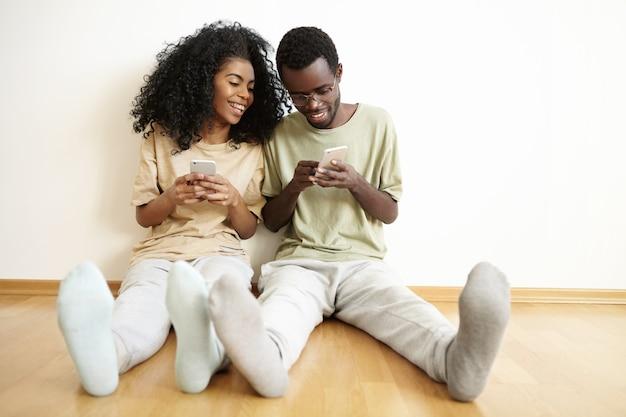 Dois melhores amigos vestindo roupas casuais se divertindo dentro de casa, sentados no chão