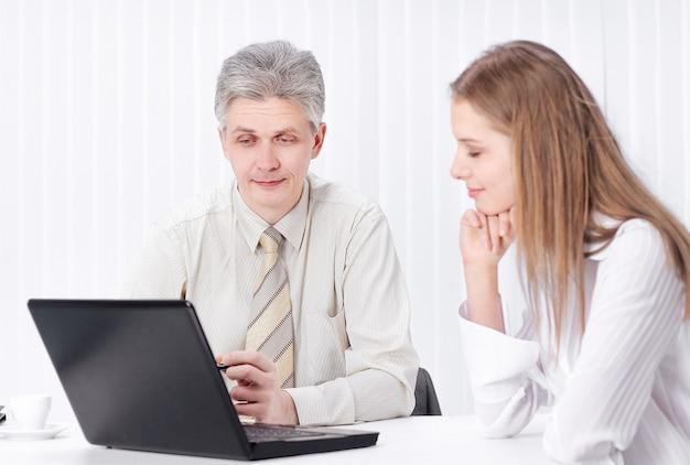 Dois membros da empresa sentados atrás de uma mesa no escritório