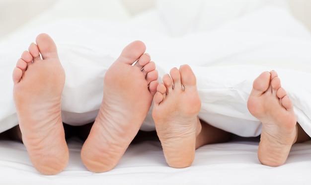 Dois, membros, de, um, família, mostrando, seu, pés, enquanto, mentindo, ligado, um, cama