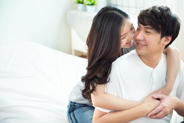 Dois menina asiática nova dos pares rebocam o homem da parte traseira na cama, pessoa romântico de ásia no amor que abraça ao sentar-se na cama, conceito do dia de são valentim com espaço da cópia.