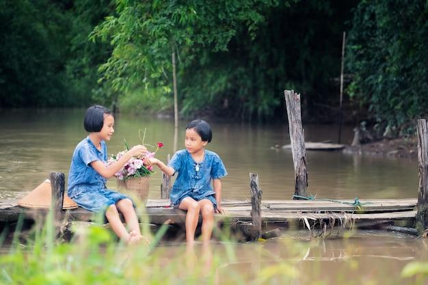 Dois, menina, crianças, sentando, e, jogando água, junto, ligado, ponte madeira, sobre, pântano
