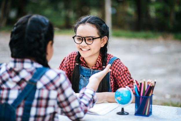 Dois, menina estudo, falando, um ao outro, em, parque