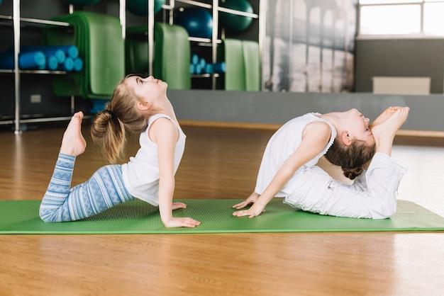 Dois, menina, prática, ioga posa, ligado, um, tapete, em, ginásio