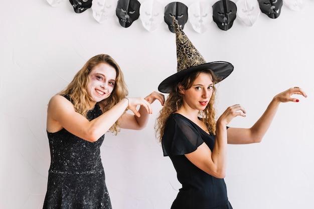 Dois, meninas adolescentes, em, dia das bruxas, trajes, com, zombie, gestos