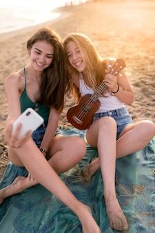 Dois, meninas adolescentes, levando, selfie, em, praia, durante, dia ensolarado